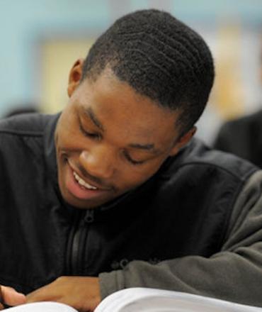 Black boy smiling while writing